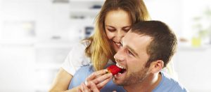 Happy young couple eating strawberries